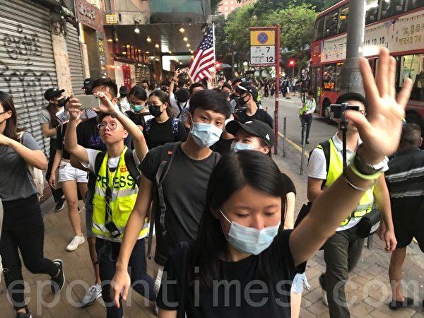 2019年10月5日,香港民眾發起港島遊行,佐敦彌敦道人鏈。人們伸出五個手指表達「五大訴求 缺一不可」。(余天祐/大紀元)