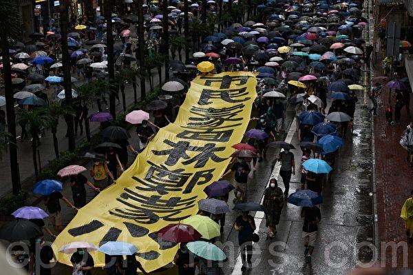 2019年10月6日,港人在港島及九龍舉行「反緊急法」大遊行。圖為港島的隊伍,民眾持「市民蒙面 林鄭蒙心」的條幅表達心聲。(文瀚林/大紀元)