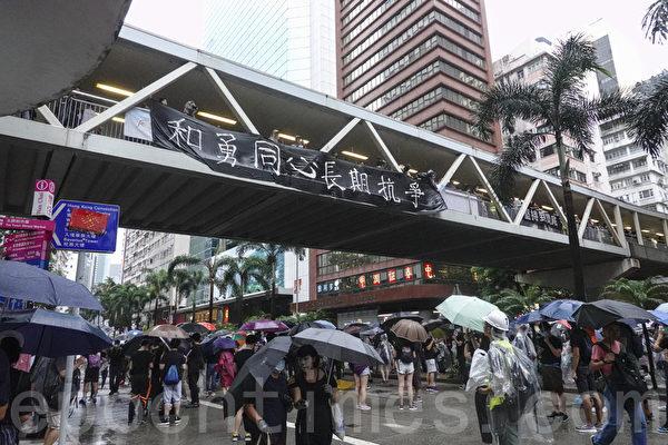 2019年10月6日,港人在港島及九龍舉行「反緊急法」大遊行。圖為港島的隊伍行經一處掛有「和勇同心 長期抗爭」標語的天橋。(余鋼/大紀元)