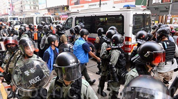 2019年10月13日,港人在18區商場進行「和勇一家 遍地開花」活動。圖為旺角彌敦道有數人被送到警車。(宋碧龍/大紀元)