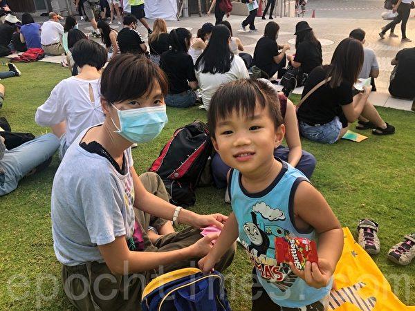 10月13日,尖沙咀海濱花園「我想香港願望紙鶴集氣大會」張女士和4歲的兒子。(梁珍/大紀元)