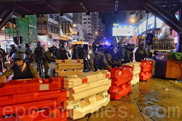2019年10月13日,港人在18區商場進行「和勇一家 遍地開花」活動。圖為旺角防暴警察推開路障準備清場。(宋碧龍/大紀元)
