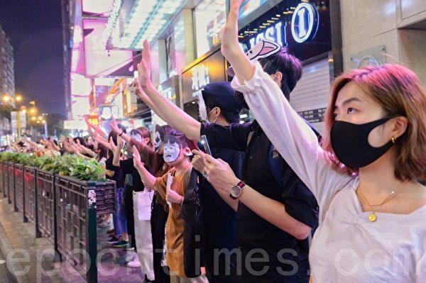 2019年10月18日,香港市民築人鏈。圖為彌敦道,民眾戴上口罩及面具,重申「五大訴求 缺一不可」。(宋碧龍/大紀元)