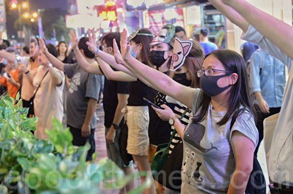 2019年10月18日,香港市民在彌敦道築人鏈。圖為抗爭者戴各種公仔麵具,重申「五大訴求 缺一不可」。(宋碧龍/大紀元)