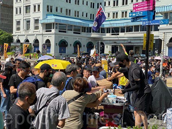香港民陣於2019年10月20日下午2點,發起「廢除惡法、獨立調查、重組警隊」大遊行,一進口的物質站,很多人排隊領口罩等,並主動捐款。(駱亞/大紀元)