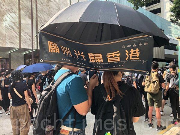 2019年10月20日,香港九龍大遊行,市民步行到尖沙咀參加遊行。圖為民眾拿著「願榮光歸香港」標語。(駱亞/大紀元)