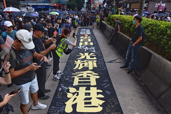 2019年10月20日,香港九龍大遊行,市民步行到尖沙咀參加遊行。圖為地上放著大橫幅標語。(宋碧龍/大紀元)
