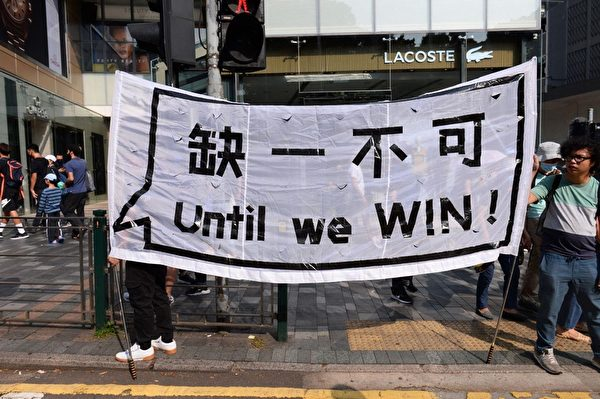 2019年10月20日,香港九龍大遊行,市民步行到尖沙咀參加遊行。圖為民眾拿著「缺一不可 Until we WIN」標語。(宋碧龍/大紀元)