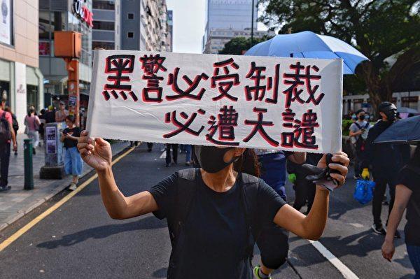 2019年10月20日,香港九龍大遊行,市民步行到尖沙咀參加遊行。圖為民眾舉著著「黑警必受制裁 必遭天譴」標語。(宋碧龍/大紀元)