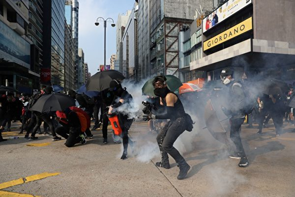 2019年10月20日,九龍區大遊行防暴警察向抗爭者發射催淚彈。(DALE DE LA REY/AFP via Getty Images)