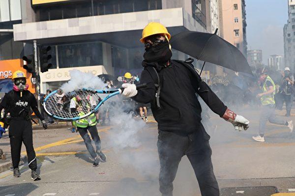 2019年10月20日,九龍區大遊行防暴警察向抗爭者發射催淚彈,一名抗議者用網球拍擊中催淚彈罐。(DALE DE LA REY/AFP via Getty Images)