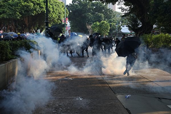 2019年10月20日,九龍區大遊行防暴警察向抗爭者發射催淚彈。(PHILIP FONG/AFP via Getty Images)