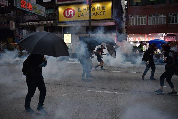 2019年10月20日,九龍區大遊行防暴警察向抗爭者發射催淚彈。(ED JONES/AFP via Getty Images)