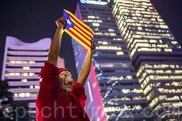 2019年10月24日晚,香港民眾於中環遮打花園發起「香港加泰人權自由集會」,聲援加泰隆尼亞人爭取自由和人權。圖為一位民眾戴上面具高舉象徵加泰隆尼亞共和國的星條旗。(余鋼/大紀元)