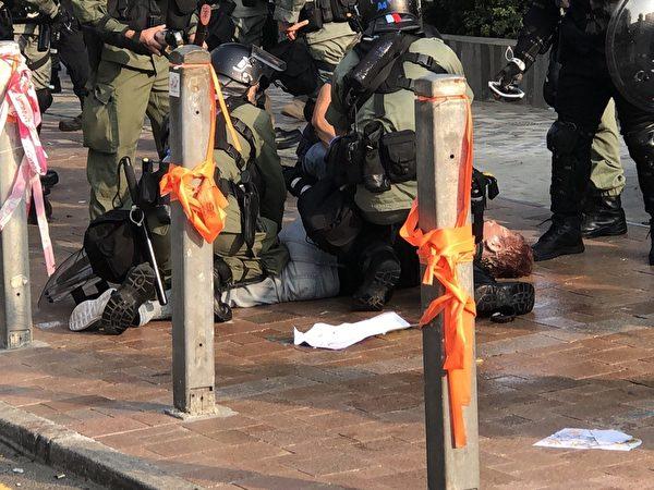2019年10月27日,香港民眾從梳士巴利花園遊行,追究警方使用暴力。圖為多位警察圍打抗爭者至昏迷。(余天祐/大紀元)