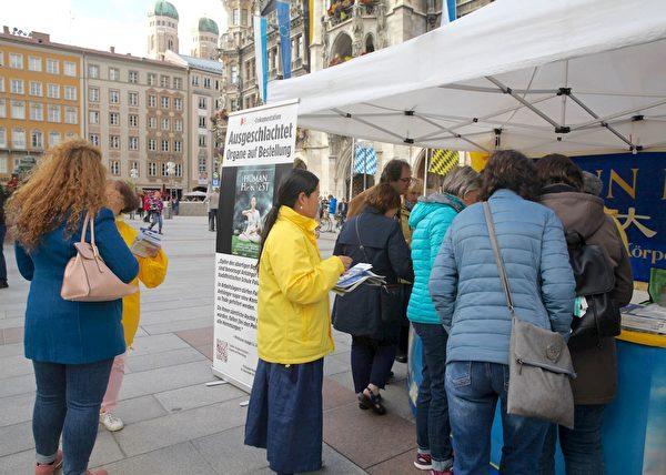 10月3日(德國統一日)在慕尼黑瑪琳廣場,人們紛紛前來了解法輪功真相。(明慧網)