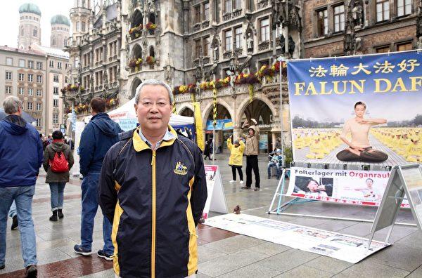 10月7日,前北京大學經濟學院副教授夏業良在慕尼黑瑪琳廣場上的法輪功信息台前。(明慧網)