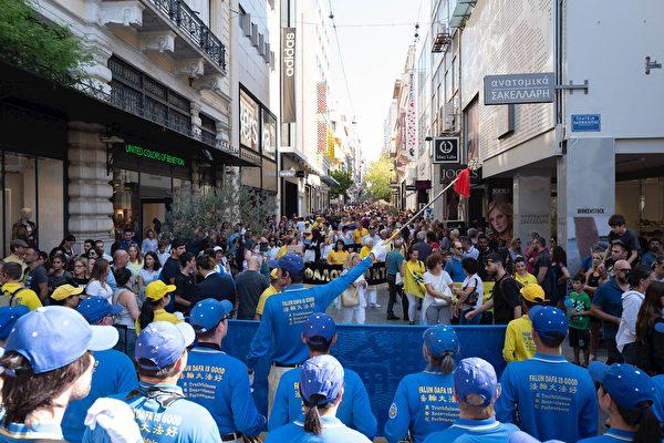 法輪功學員的遊行隊伍穿過雅典老街區和購物區,路人紛紛駐足觀看,攝影留念。(明慧網)