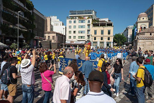 法輪功學員的遊行隊伍穿過繁華的市中心。觀眾紛紛拍照、留影。(明慧網)