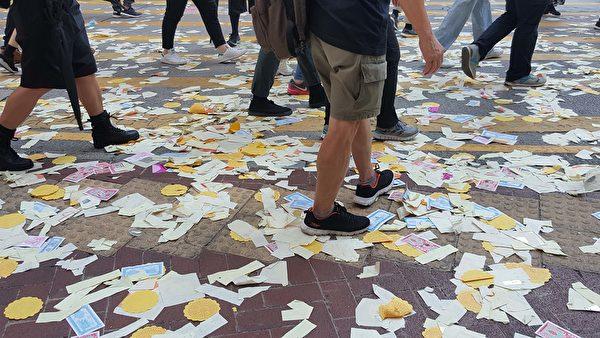 2019年10月1曰,香港銅鑼灣軒尼詩道,參加遊行民眾送走中共最後一程,滿地紙錢。(林志龍/大紀元)