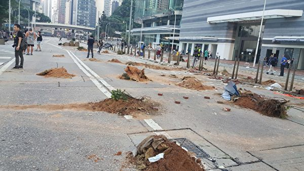 2019年10月1曰,香港金鐘,參加遊行民眾堆起像墳墓土堆的障礙物。(林志龍/大紀元)