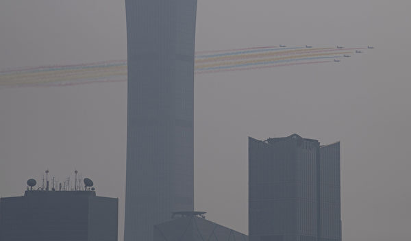 10月1日中共舉行閱兵式,北京城籠罩在陰霾之中。彩色飛機陣罩在灰濛蒙的陰霾中。 (NOEL CELIS / AFP)