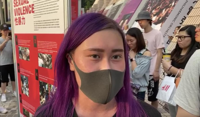 尖沙咀海邊觀看「警方濫用暴力和侵犯人權展」的香港女青年。(駱亞/大紀元)