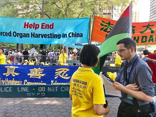 Fox News媒體記者亞當・蕭(Adam Shaw,右)站在「請幫助結束發生在中國的大屠殺」(Help End Genocide in China)條幅前,採訪法輪功學員簡(Jane)。(李桂秀/大紀元)