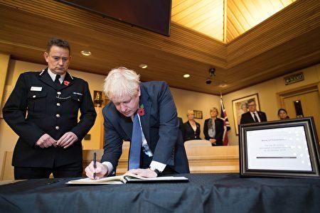 英國首相鮑里斯·約翰遜(Boris Johnson)在2019年10月28日對倫敦東部瑟羅克(Thurrock)的瑟羅克議會辦公室進行訪問期間,在給英國卡車39屍案的遇難者的慰問書上留言。(STEFAN ROUSSEAU/POOL/AFP via Getty Images)