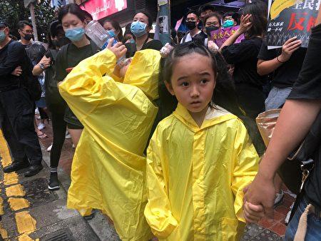 一位市民帶著7歲的女兒(梁珍/大紀元)