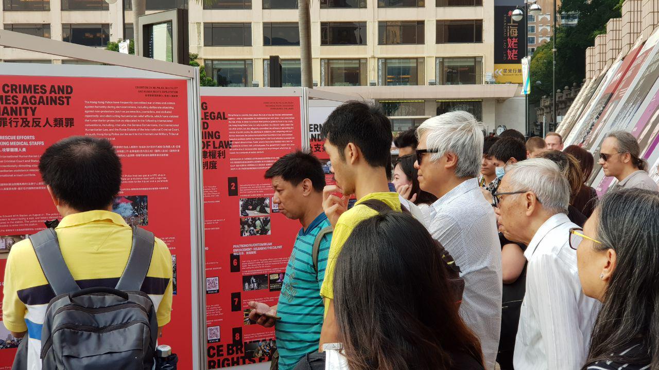 民間在尖沙咀的海邊舉行「香港警察濫用暴力和侵犯人權展」,吸引了很多人駐足觀看。(駱亞/大紀元)