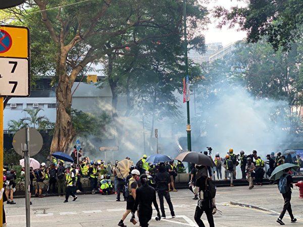 2019年10月20日,九龍區大遊行防暴警察向抗爭者發射催淚彈。(駱亞/大紀元)