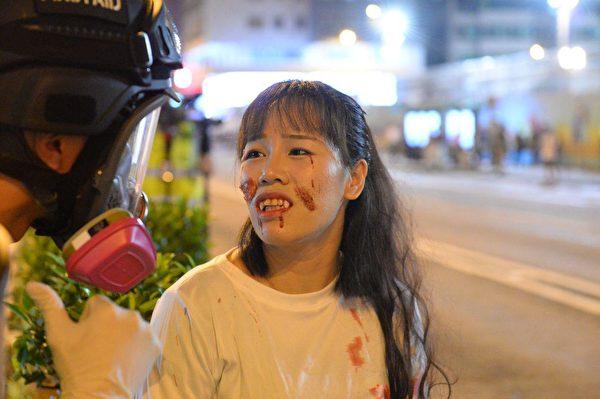 彌敦道有一女子被防暴警察鎮壓受傷,臉部受傷流血。(宋碧龍/大紀元)