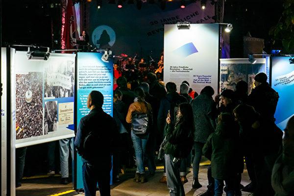 11月4日晚,民眾在柏林亞歷山大廣場觀看「和平革命-柏林牆倒」圖片展,這是慶祝柏林牆被推翻30周年慶祝活動周的內容之一。(張清颻/大紀元)