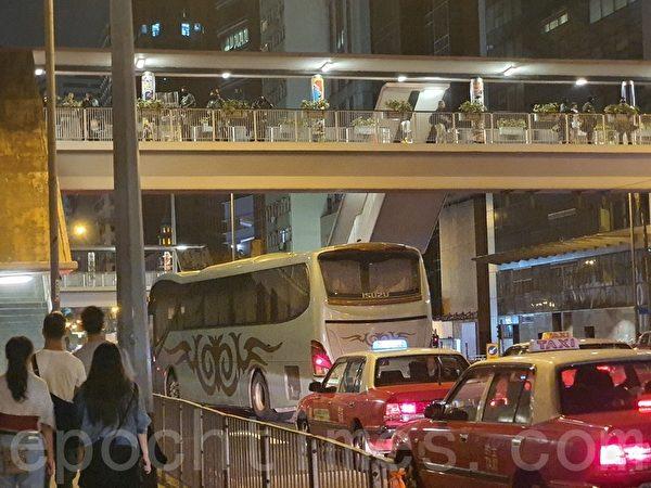 2019年10月31日晚是港府「禁蒙面」惡法實施以來首個萬聖節,香港民眾在中環蘭桂坊發起戴面具行動。橋上有防暴警察戒備。(孫明國/大紀元)