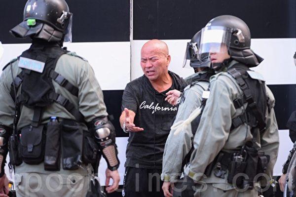 11月2日,香港銅鑼灣黑衣男被警方用楜椒噴霧噴眼和搜查。(宋碧龍/大紀元)