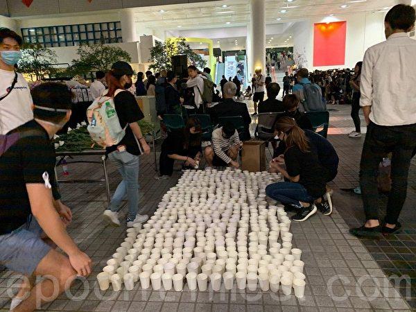 2019年11月8日,香港科大學生設立悼念周同學的祭壇。圖為科大學生準備燭光悼念。(韓納/大紀元)
