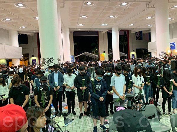 2019年11月8日,香港科大學生設立悼念周同學的祭壇。圖為科大學生為周同學默哀。(韓納/大紀元)