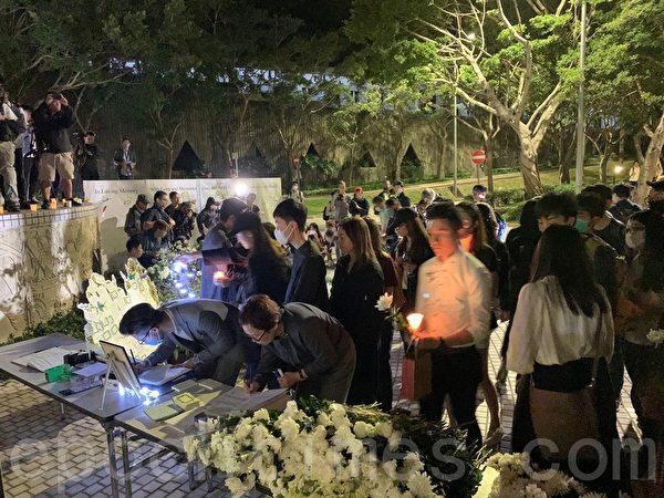 2019年11月8日,香港科大學生設立悼念周同學的祭壇。圖為科大學生為周同學獻花。(韓納/大紀元)