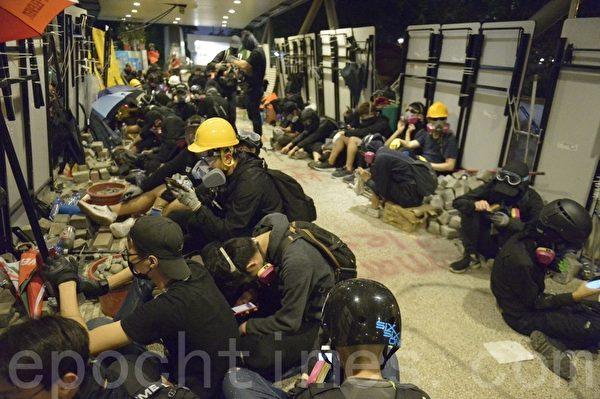 2019年11月12日,香港繼續「三罷」行動。警察不斷向香港城市大學宿舍發射催淚彈,學生在天橋上從高處向地面扔擲磚塊等予以反擊,抵擋港警進入。(余天祐/大紀元)