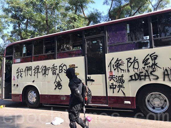 2019年11月13日,香港警察闖進香港各大學狂轟濫捕青年學生。學生日夜扺抗。圖為中大校車「天滅中共」「我們捍衛香港」標語。(余鋼/大紀元)