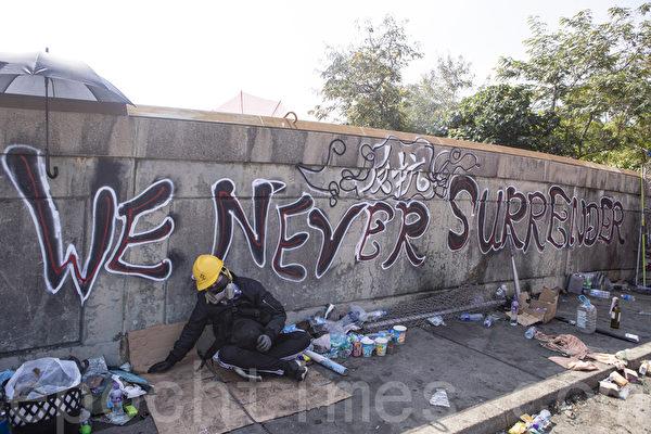 2019年11月13日,警察闖進香港各大學校園,狂轟濫捕青年學生。學生日夜扺抗。圖為中大學生在牆上噴寫「我們絕不投降」標語。(余鋼/大紀元)