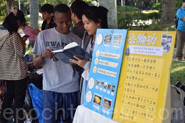 法輪大法社在台大校園擺攤,法輪功學員向台大外籍學生洪法。(台大法輪大法社提供)
