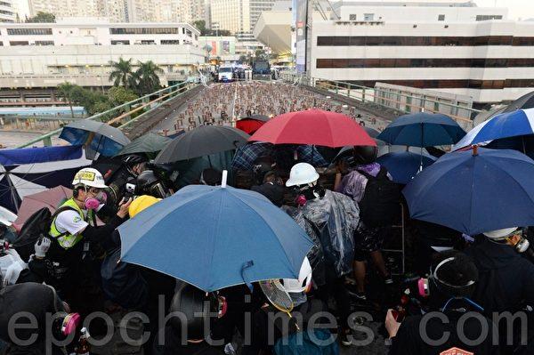2019年11月17日,香港尖東橋學生用傘做掩護。(宋碧龍/大紀元)