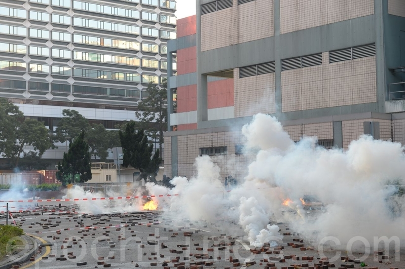2019年11月18日早上,理大抗爭者約好外撤,外面有防暴警察用催淚彈驅趕。(宋碧龍/大紀元)