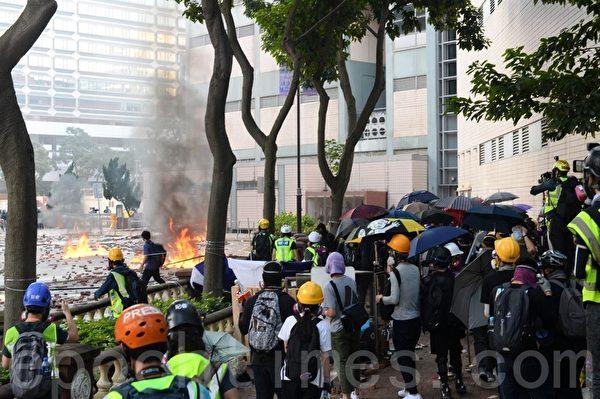 2019年11月18日早上,理大抗爭者約好外撤,可是還沒有走到警方的防線就被警方的催淚彈驅散,又不得不退回校園內。圖為第2次外撤。(宋碧龍/大紀元)