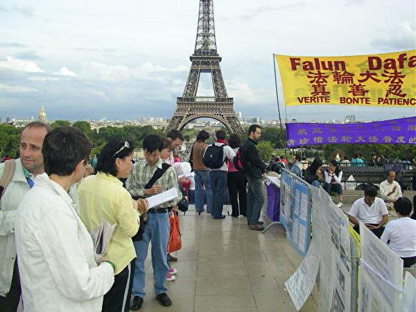 在巴黎埃菲爾鐵塔前,大陸遊客看法輪功真相展板。(明慧網)