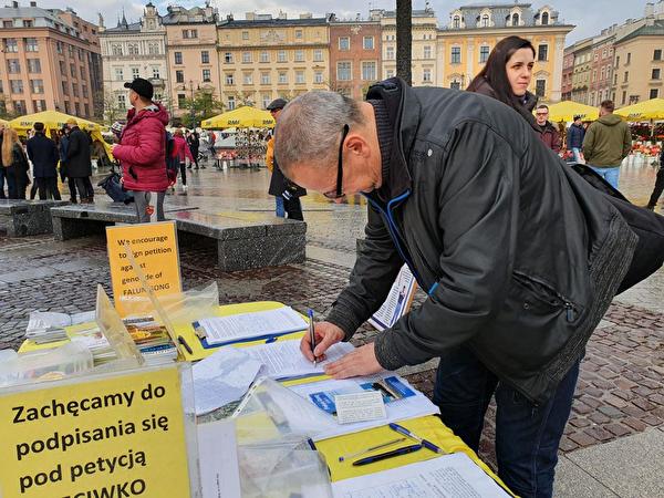 2019年11月9日至10日多國遊客冒雨簽名支持法輪功反迫害。(明慧網)
