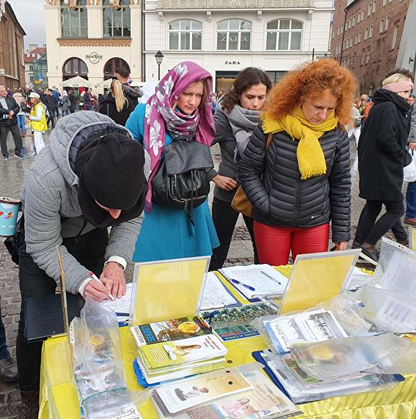 波蘭法輪功學員在克拉科夫市古城中央市集廣場向遊客展示功法,各國遊客簽名支持他們揭露中共迫害,舉報元兇江澤民。(明慧網)