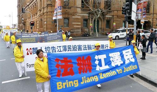 多年來,在全澳各地舉行的遊行等反迫害活動中,要求「法辦江澤民」是法輪功學員的主要訴求之一。圖為2018年9月7日在悉尼市中心舉行的大遊行中,學員展示「法辦江澤民」和「全球控告迫害元凶江澤民」的橫幅。(大紀元)